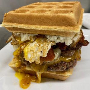 """Double Waffle Double: Double bacon cheeseburger topped with sriracha spiked maple syrup and an over easy fried egg between two warm Belgian waffles slathered with """"everything bagel"""" cream cheese"""