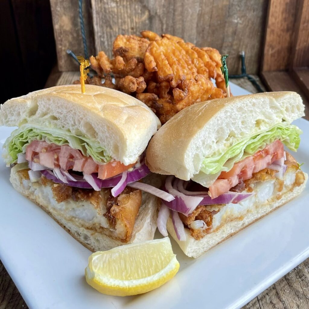 The Crispy Cod Stacker Beer battered cod, crispy waffle fries, lettuce, tomato, red onion and tartar sauce on a super soft Chaves bakery Portuguese roll