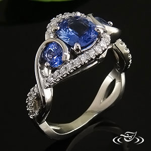 Sapphire ring with cushion cut 1.12ct unheated sapphire & 2 round 4mm (.59ctw) sapphires. Surrounded by Micro-pave set diamonds