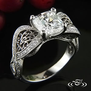 Organic sweep shank ring with bead set diamonds, hand fabricated filigree in openings, and channel set side stones with criss cross pattern.