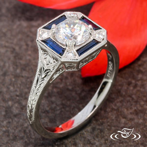 Platinum antique inspired design with custom cut bagguette sapphires and (4) 1.6mm accent diamonds totaling .06ctw. Wheat engraving on outside and piece filigree design on sides. Center can be set with the diamond of your choice ~.75-0.90ct.