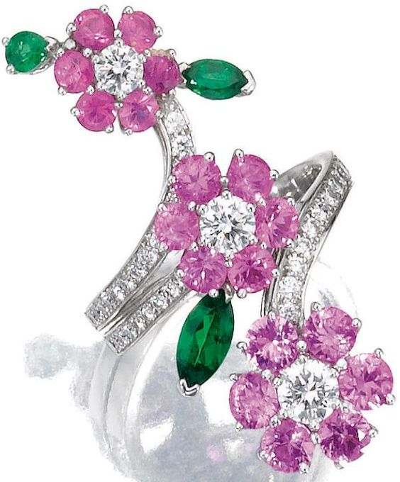 Gem-set and diamond ring, Van Cleef & Arpels. Designed as three flowers set with circular-cut pink sapphires, pear- and marquise-shaped garnets, highlighted with brilliant-cut diamonds, mounted in white gold, size 56, signed Van Cleef & Arpels and numbered, French assay and partial maker's marks, accompanied by fitted case signed Van Cleef & Arpels.