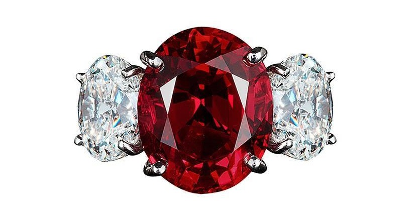 A ring centered upon a fiery 8 carat imperial red Thai ruby flanked by oval diamonds