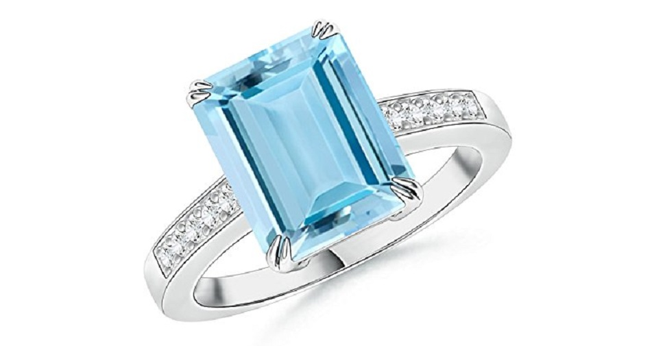 The emerald-cut aquamarine is held in a double claw prong setting and has a serene sea blue hue. Shimmering pave set diamonds embellish the shank and accentuate the sparkling aquamarine. This aquamarine cocktail ring is crafted in 14k white gold.