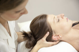Osteopath or Physiotherapist treating her patient's neck area