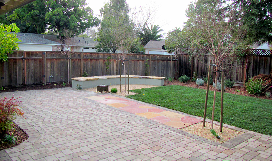 Backyard view of lawn, pavers, patio, maasonry bench