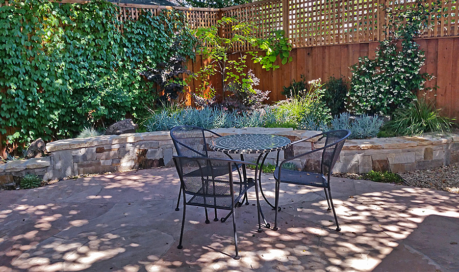 Private residential backyard with masonry wall, stone patio, wood fence, plants, low-voltage lighting, and irrigation system provided by Modern Gardens Landscaping