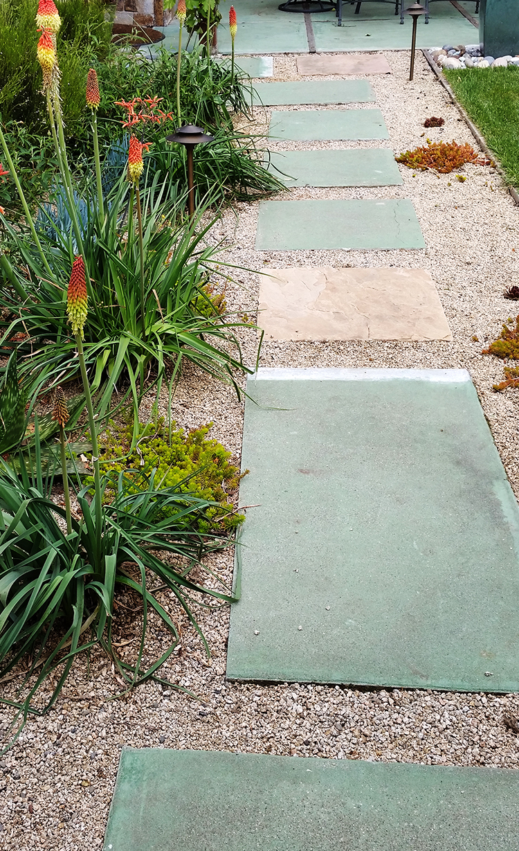 Recycled Concrete walkway next to red hot pokers and other flowers and foliage