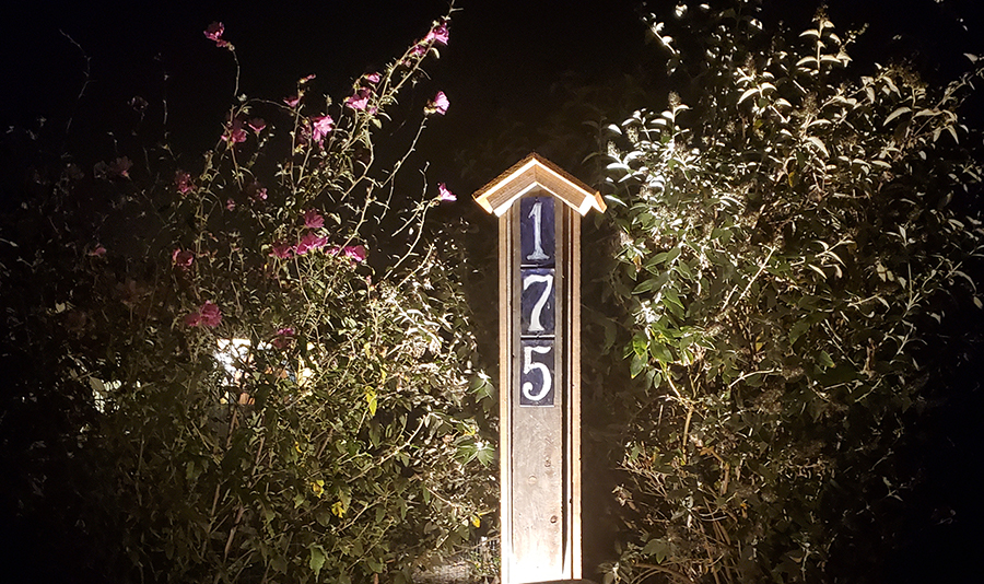 Address sign at night lit up by low voltage lighting