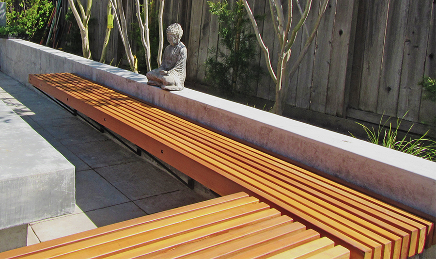 Two slatted wooden benches connected at 90 degree angles attached to a masonry wall with a statue of a meditating Buddhist on top of the masonry wall