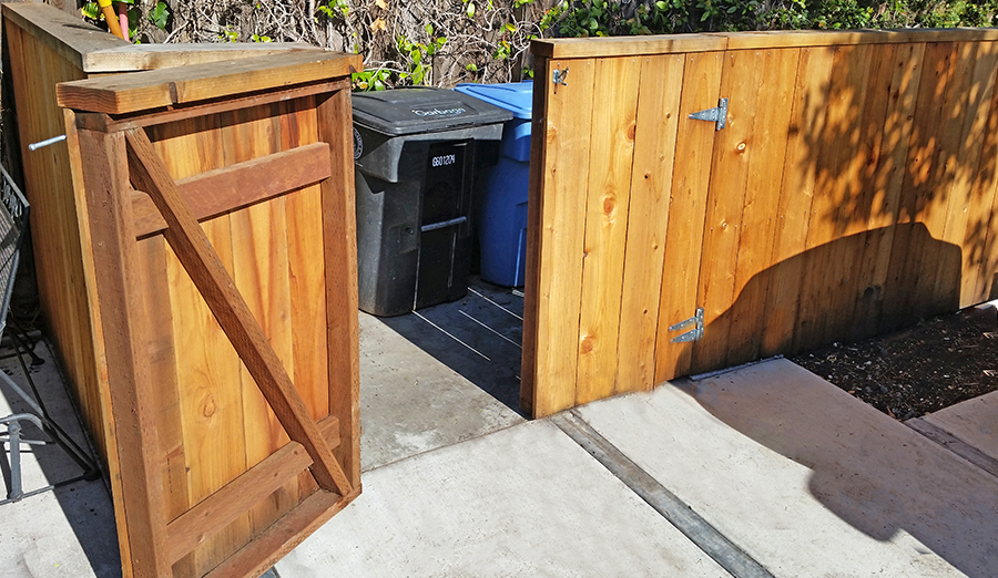fence and gate built around garbage area with garbage cans in the background