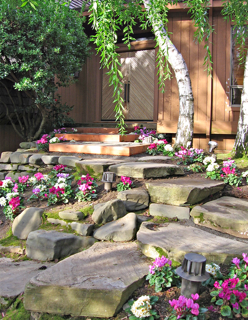 Stone pathway surrounded by cyclamen and other flowers winding to a small porch and entrance