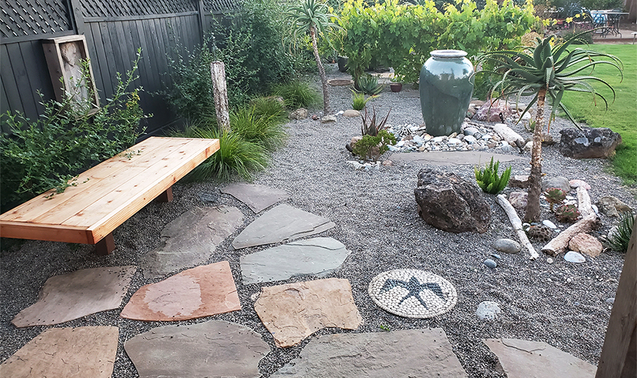 The rock and stone pathway, plants, and ornamental fixtures in one of the gardens at Modern Gardens Landscaping