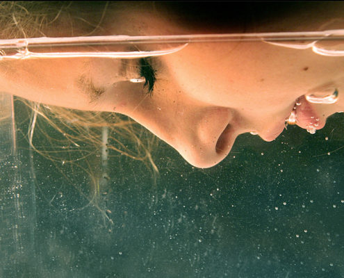 This image of a girl's face underwater holding breath is used as the header for the conscious breathing article on the Ultimate Healing Guide of TheBodyIsMind.com website
