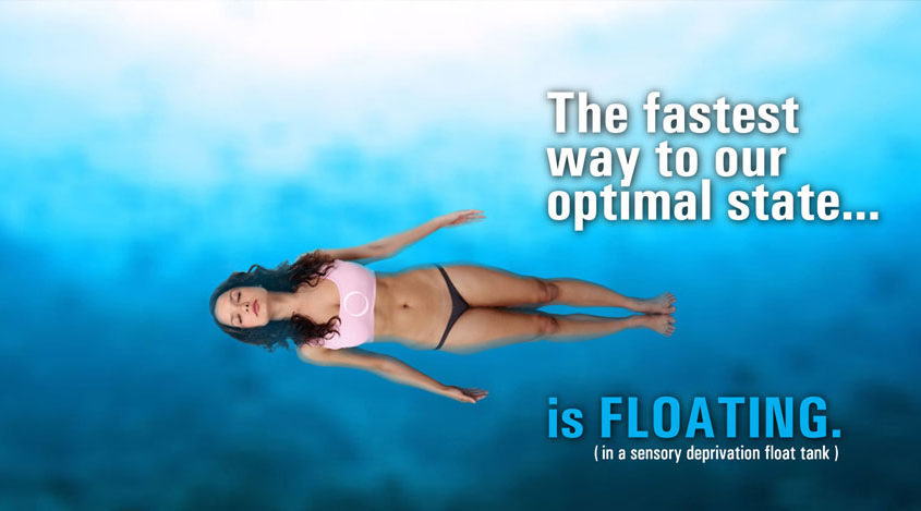 floatation-therapy-floating-article-button this image shows a drone view of a dark-haired woman wearing a sports bikini bottom and sport top is floating in the most beautiful blue water. Click this button to read the article on Floatation Therapy here on TheBodyIsMind
