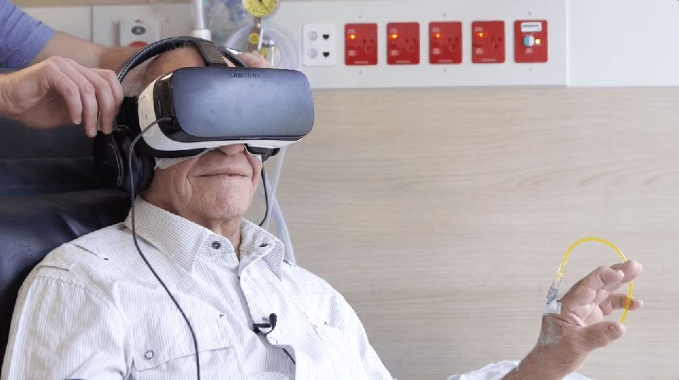 virtual-reality-therapy-hospital - an old man getting an iv treatment watches distracting entertainment on a stand-alone Samsung VR gear
