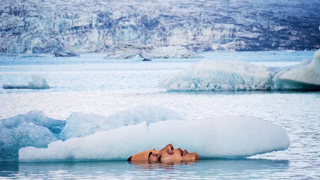 This picture of Sean Yoro's The Warning of a face painted on glacial ice depicts a woman submerged and floating in glacial icewater, and is used as the header image of TheBodyIsMind Wim Hof Method article.