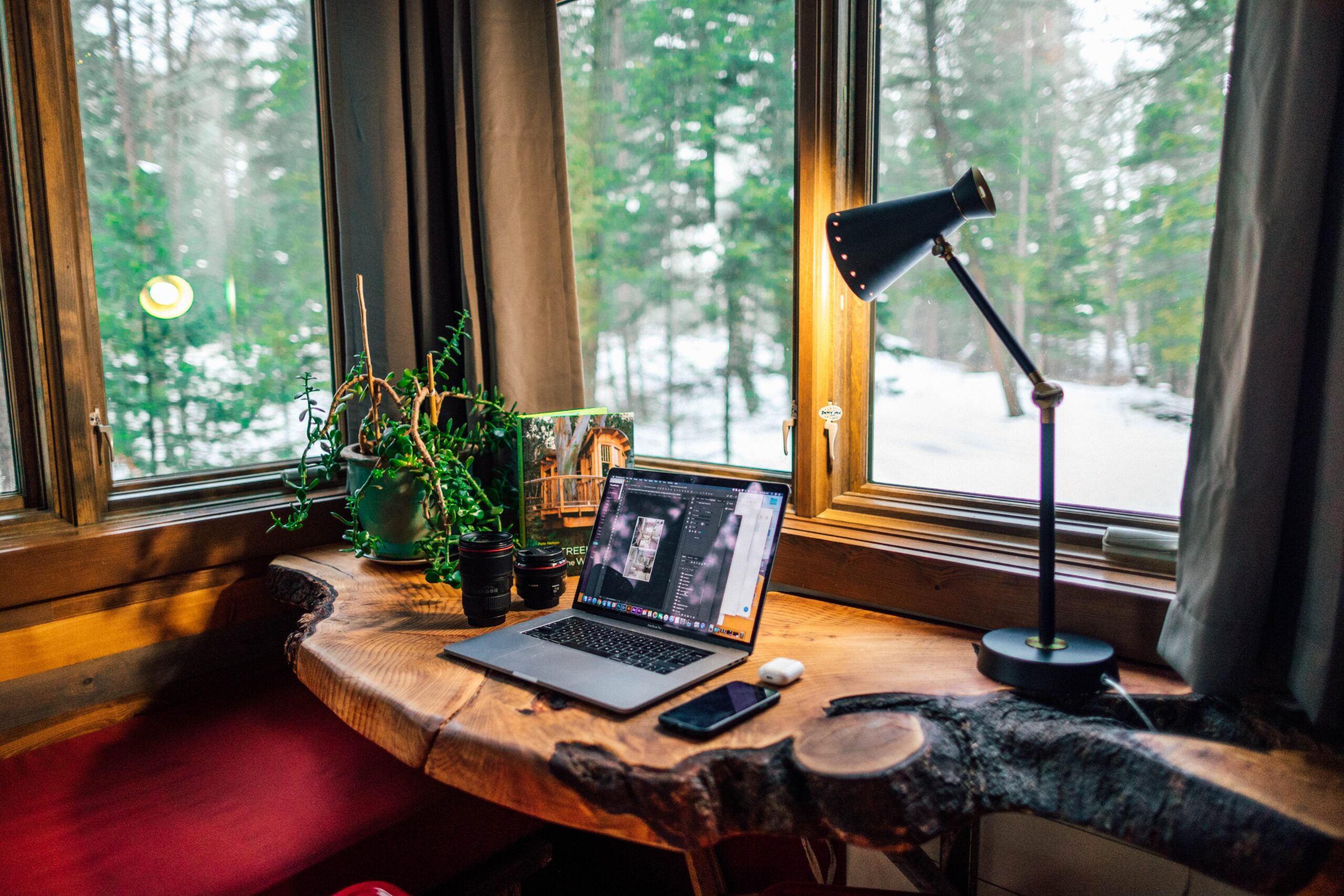 home office setup with laptop and lamp on wooden desk by window or remote workforce