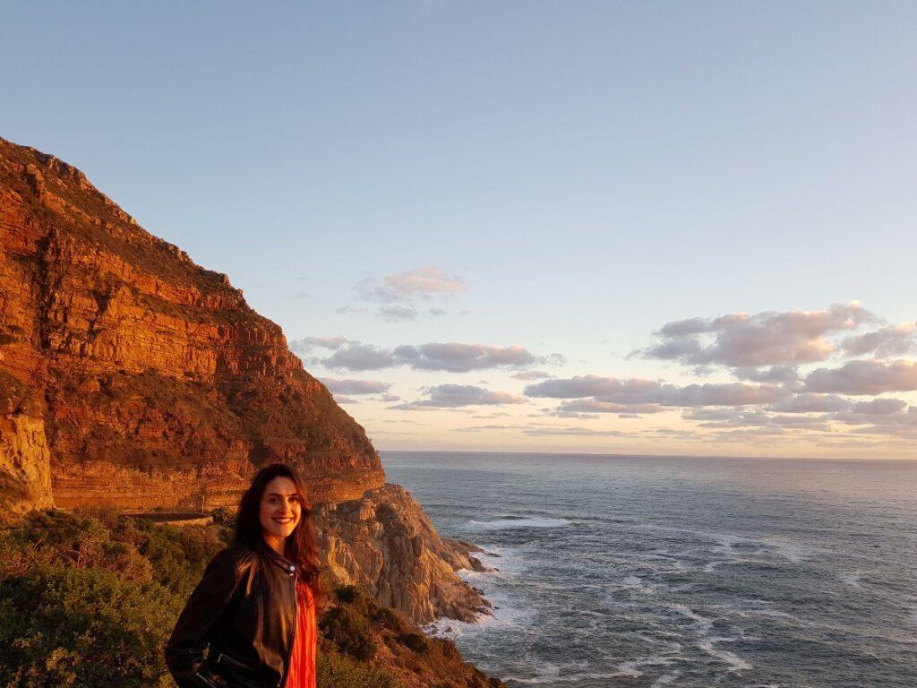 Mulher contemplando pôr do sol com montanha e mar ao fundo