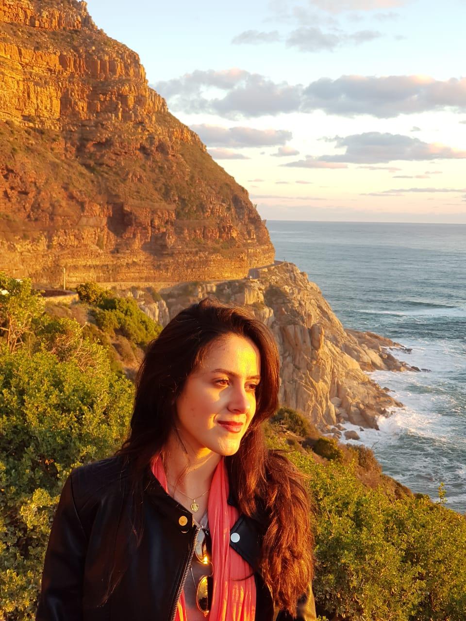 Mulher olhando pôr do sol na Chapmans' Peak Drive, África do Sul