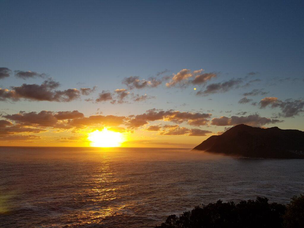 Mar e pôr do sol na Chapman's Peak, África do Sul