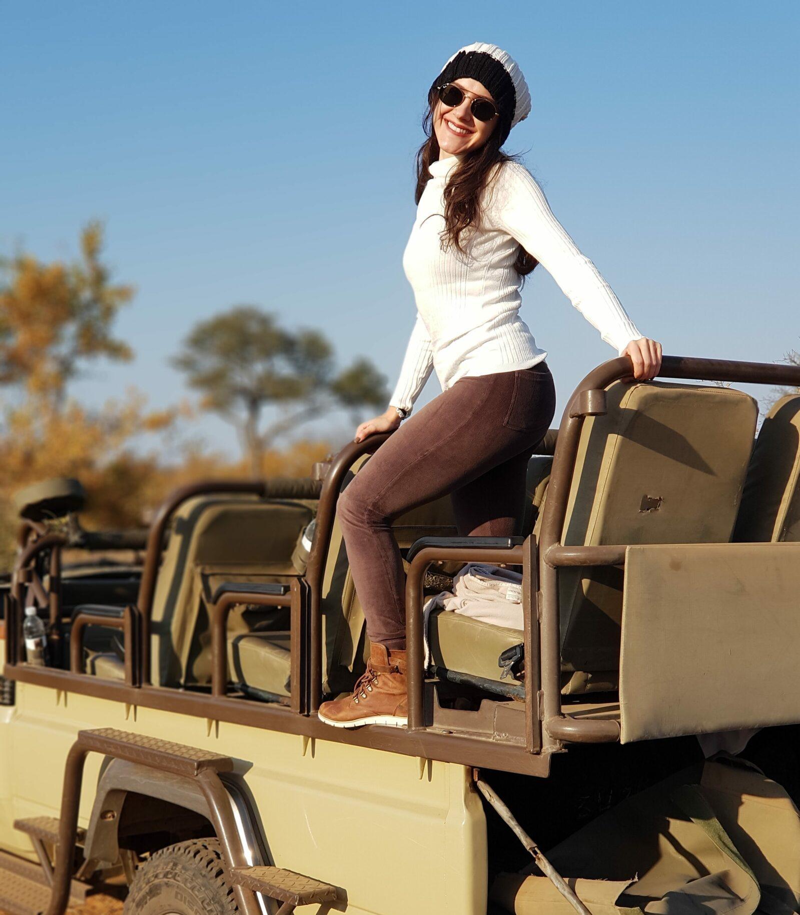 Mulher em pé em carro de safari na África do Sul