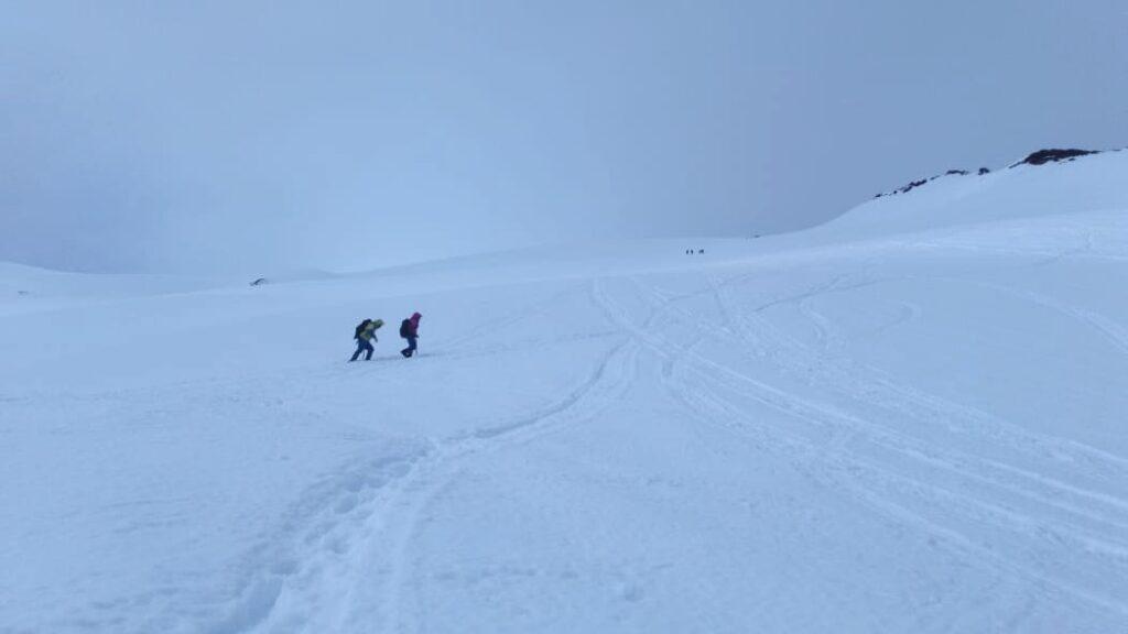 casal subindo vulcão tomado por neve no Chile