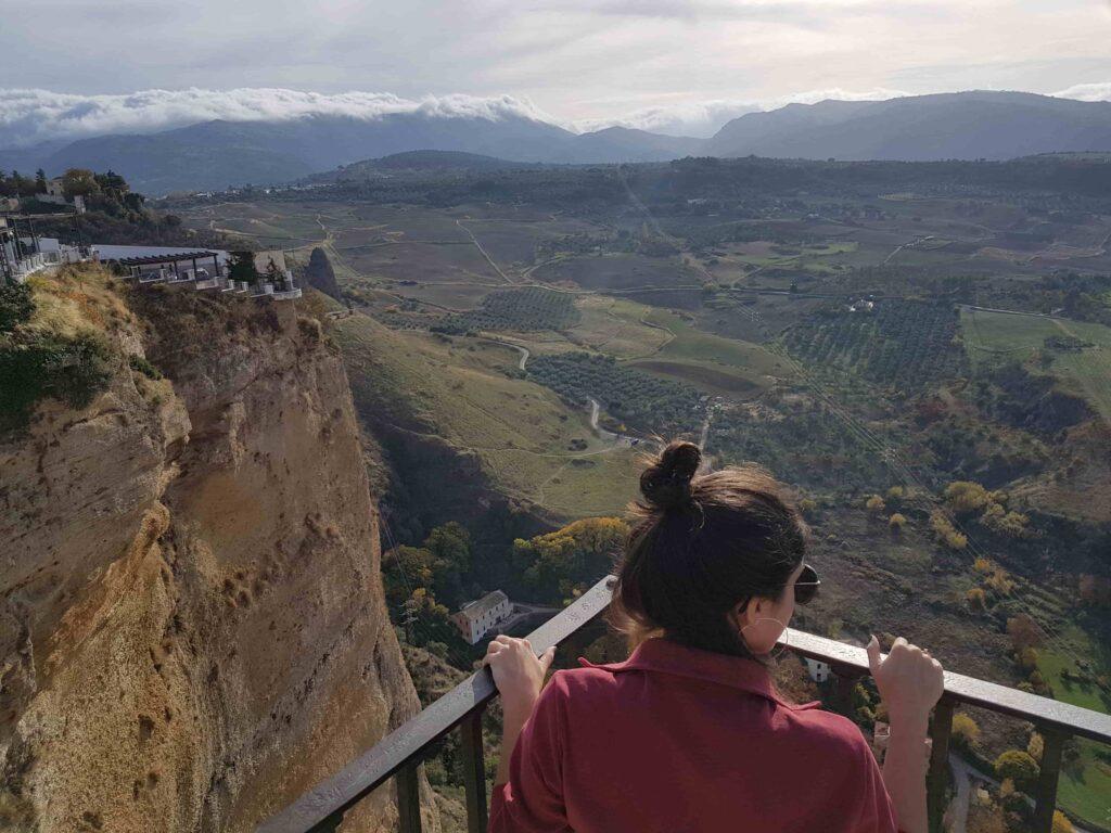 Mulher jovem em miradouro olhando cidade que fica em um alto penhasco