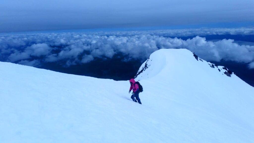 Mulher escalando vulcão cheio de  neve no Chile