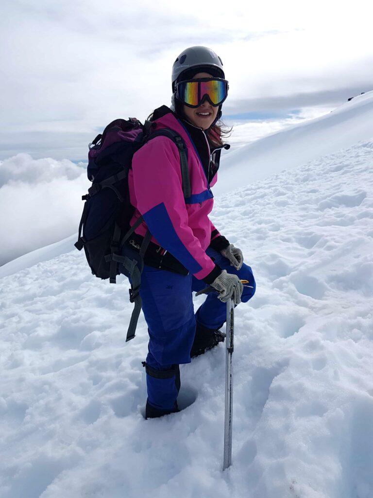 Mulher subindo vulcão cheio de neve
