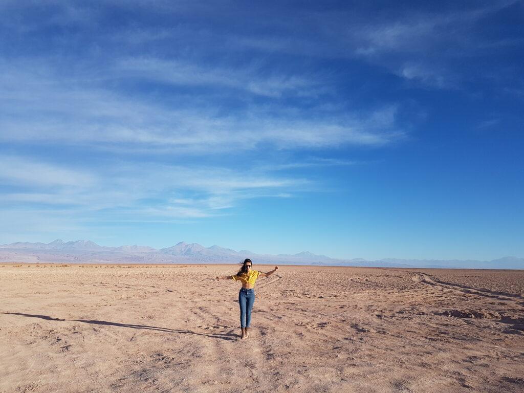 moça andando com os braços abertos no deserto