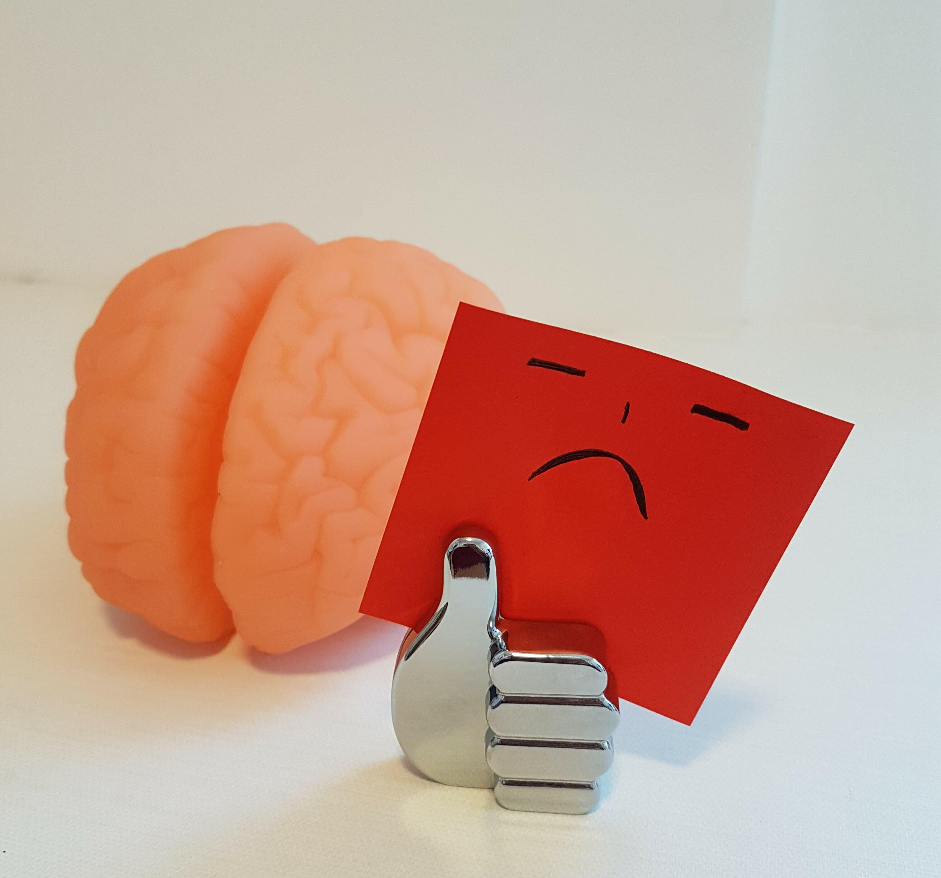 Cérebro e papel com desenho de rosto triste