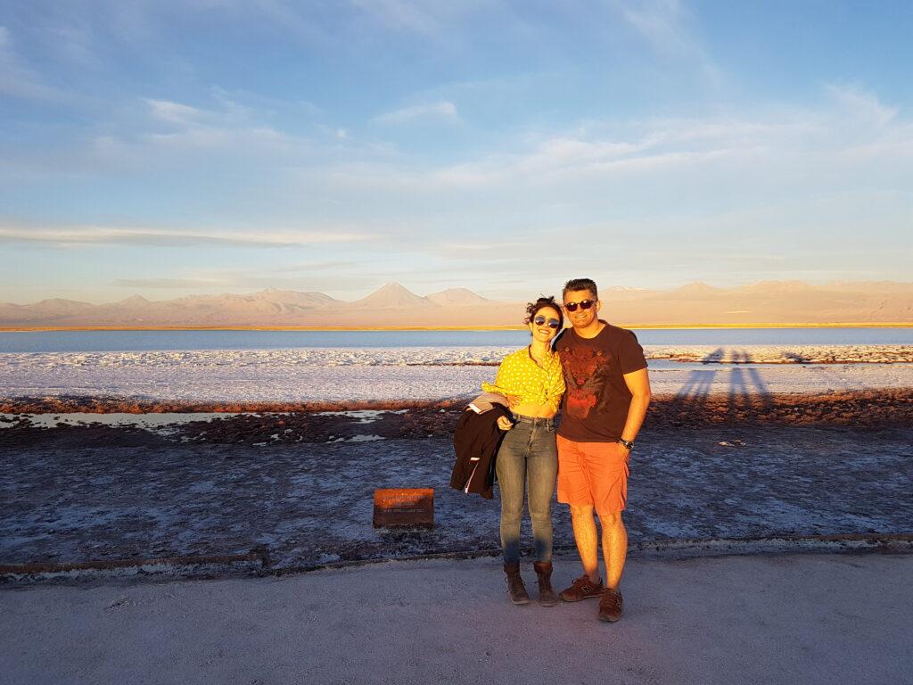 Casal no deserto com lagoa de sal ao fundo