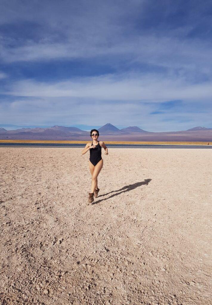 Mulher jovem correndo feliz na Laguna Cejar no deserto