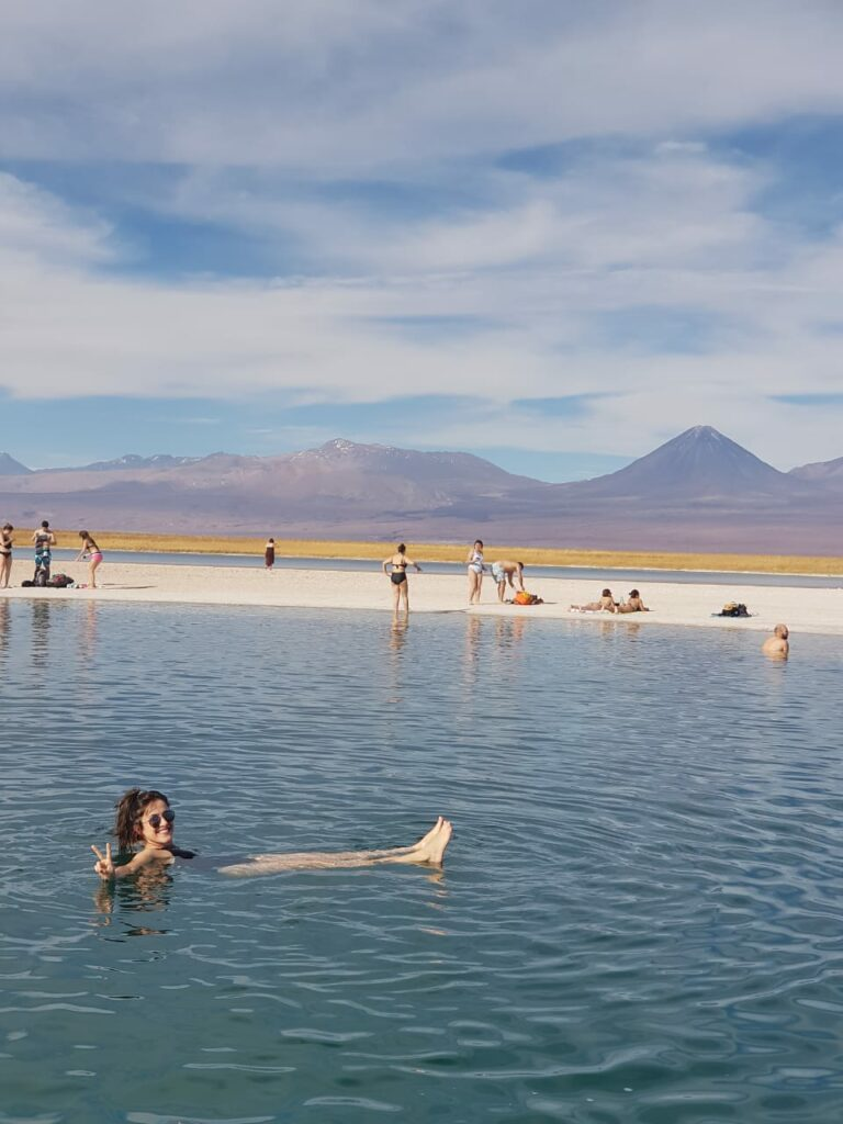 Moça feliz flutuando na Laguna Cejar com vulcão ao fundo