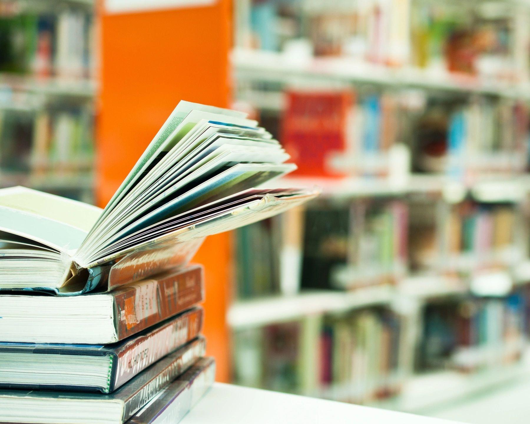 Livros em uma mesa e estante de livros ao fundo