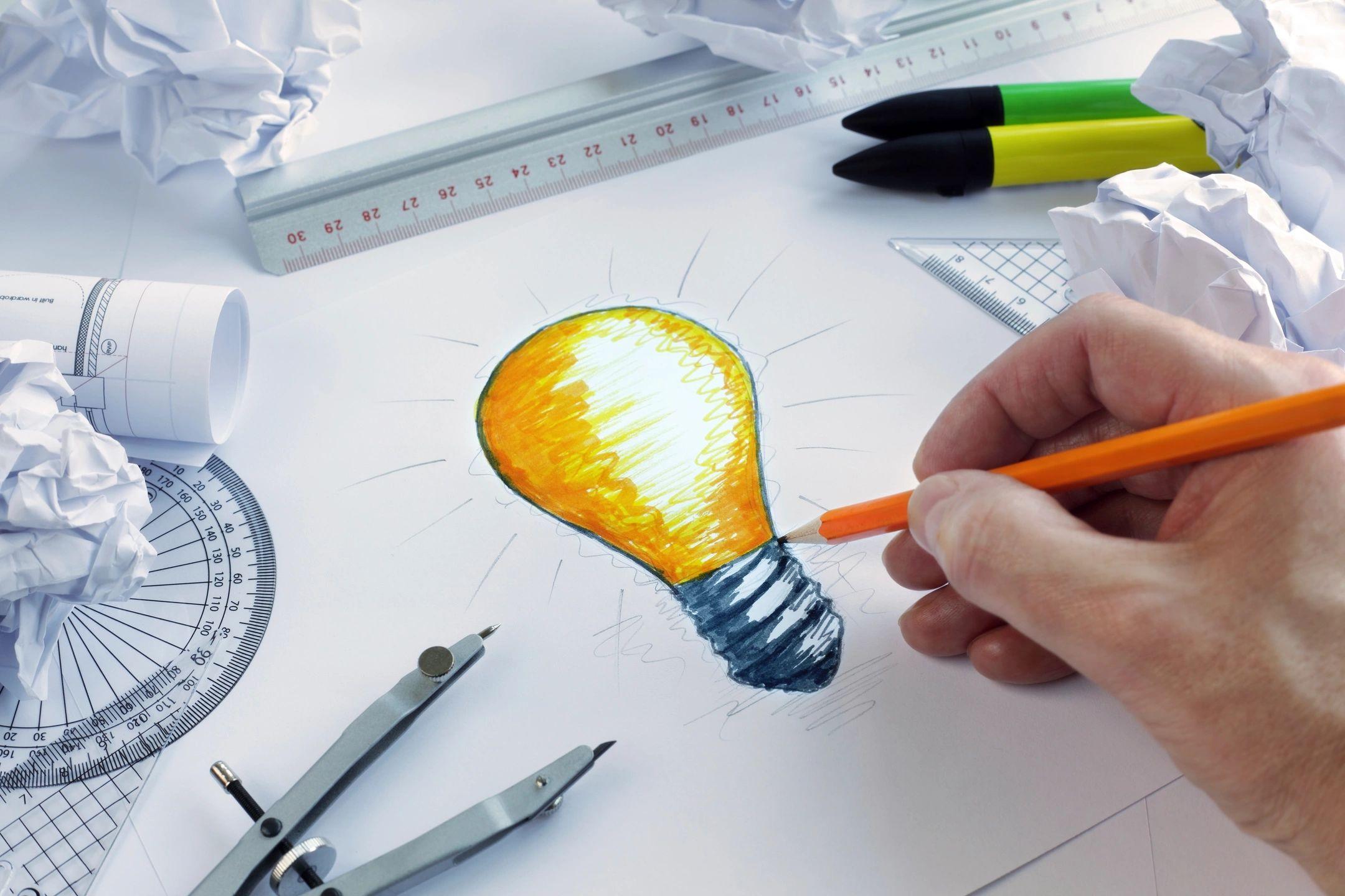 Mão desenhando uma lâmpada iluminada