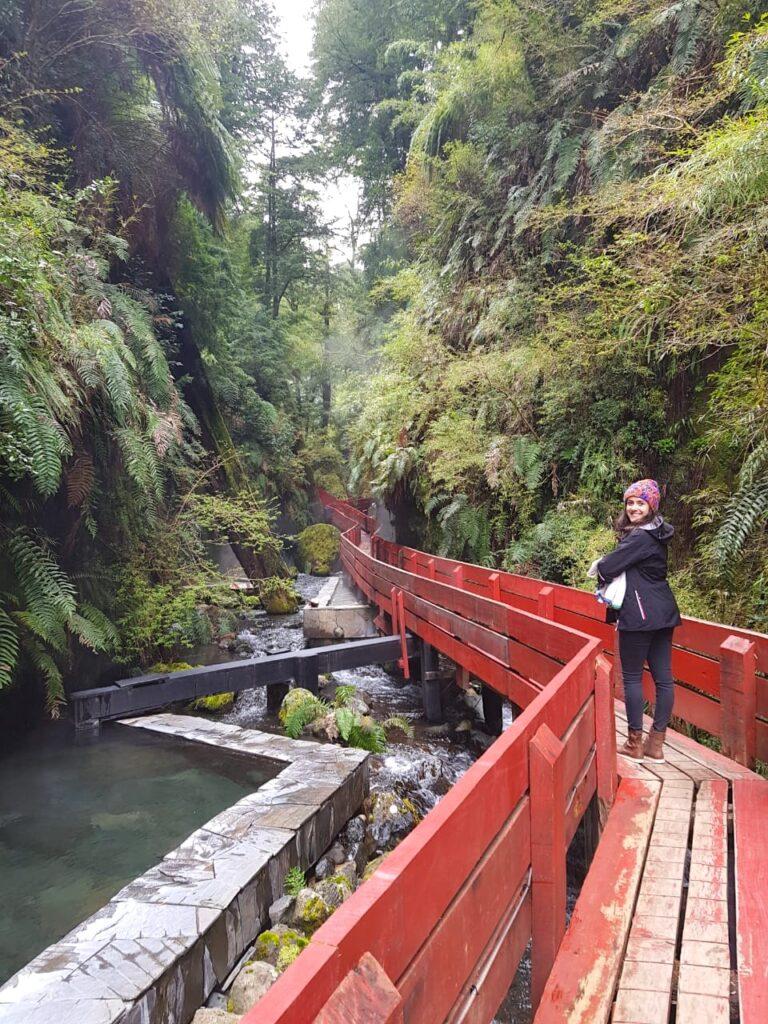 Mulher parada m longa passarela de madeira vermelha no meio da floresta e sob rio de água quente natural