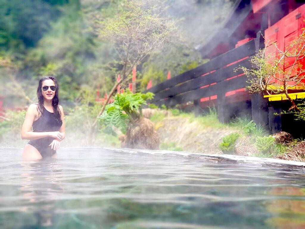 Mulher parcialmente dentro de piscina natural de água quente no meio da mata