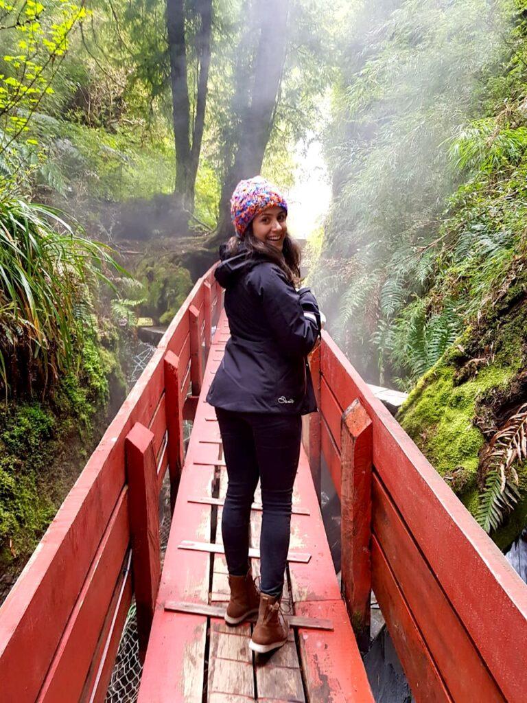 Mulher em uma passarela vermelha no meio da natureza e de um rio de água quente saindo fumaça