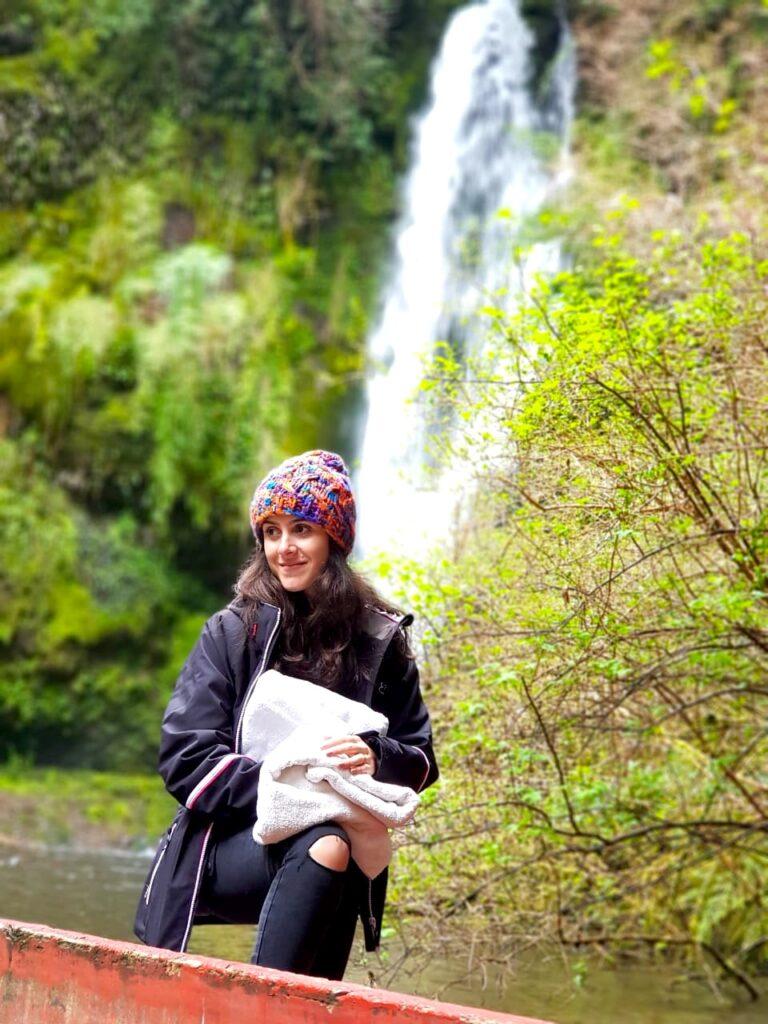 Mulher na floresta com cachoeira ao fundo