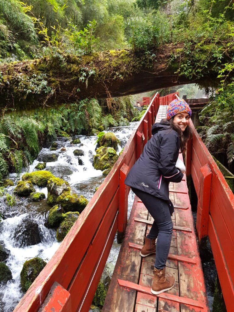Mulher passando em passarela de madeira vermelha com rio embaixo