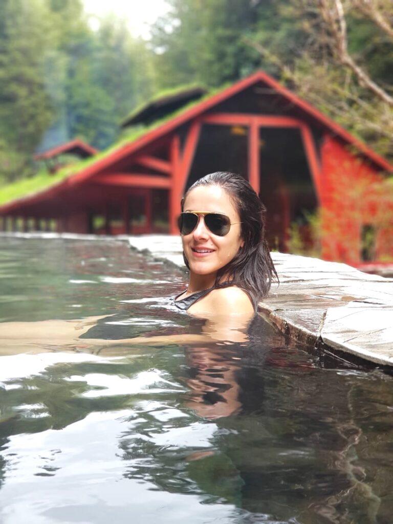 Termas Geométricas, Chile. Mulher em piscina de água quente natural com linda natureza ao fundo