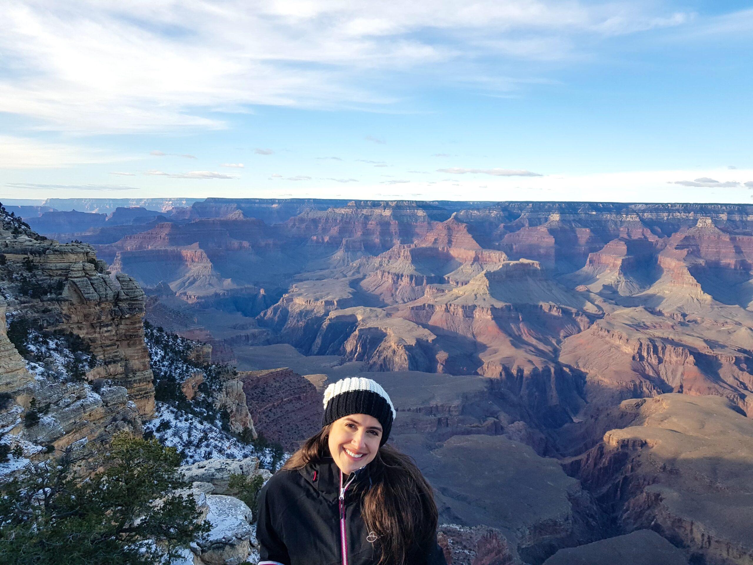 Mulher sorrindo e ao fundo ampla paisagem do Grand Canyon