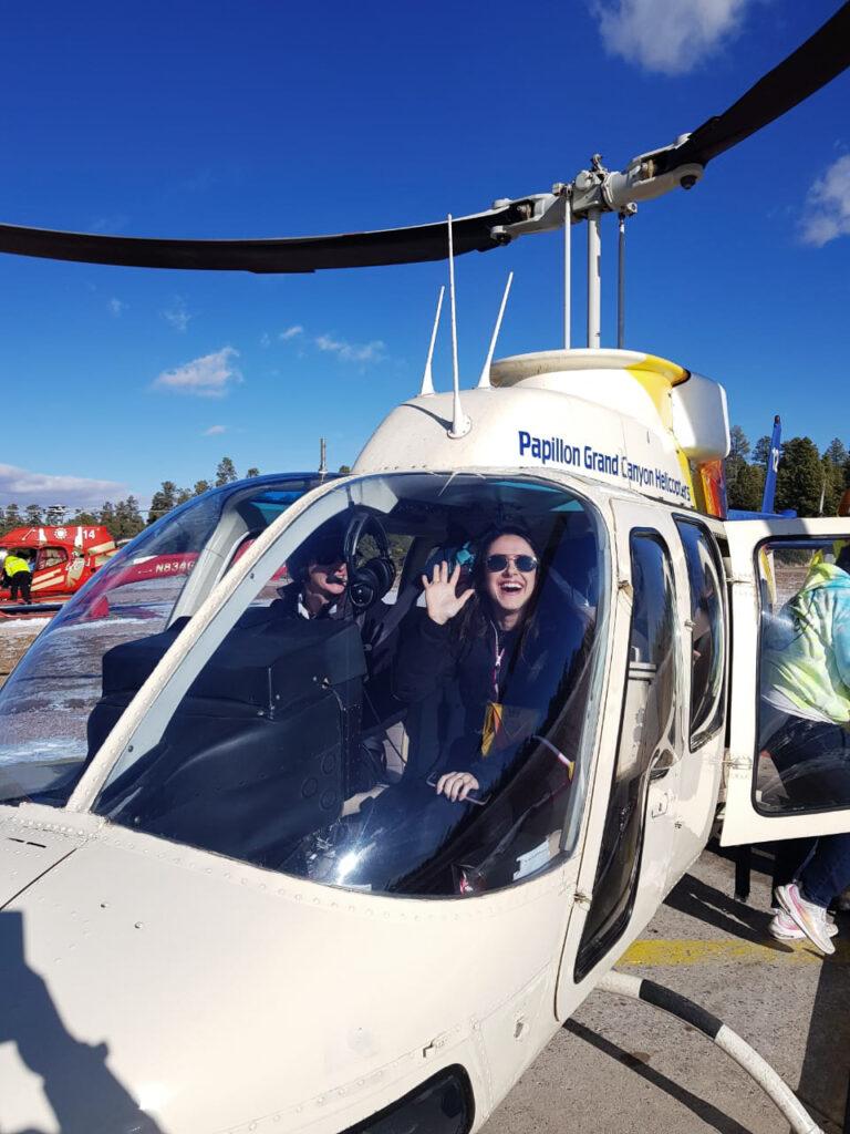 Moça sorrindo dentro de helicóptero junto com pilota depois de sobrevoar o Grand Canyon