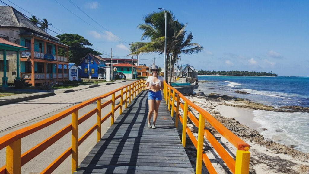 Mulher em passarela amarela na Ilha de San Andres, com mar do caribe ao fundo