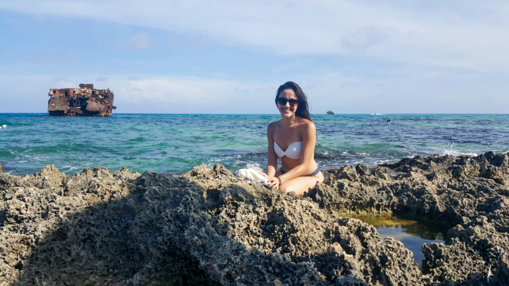 Mulher na Ilha de San Andres e dois navios encalhados ao fundo no mar
