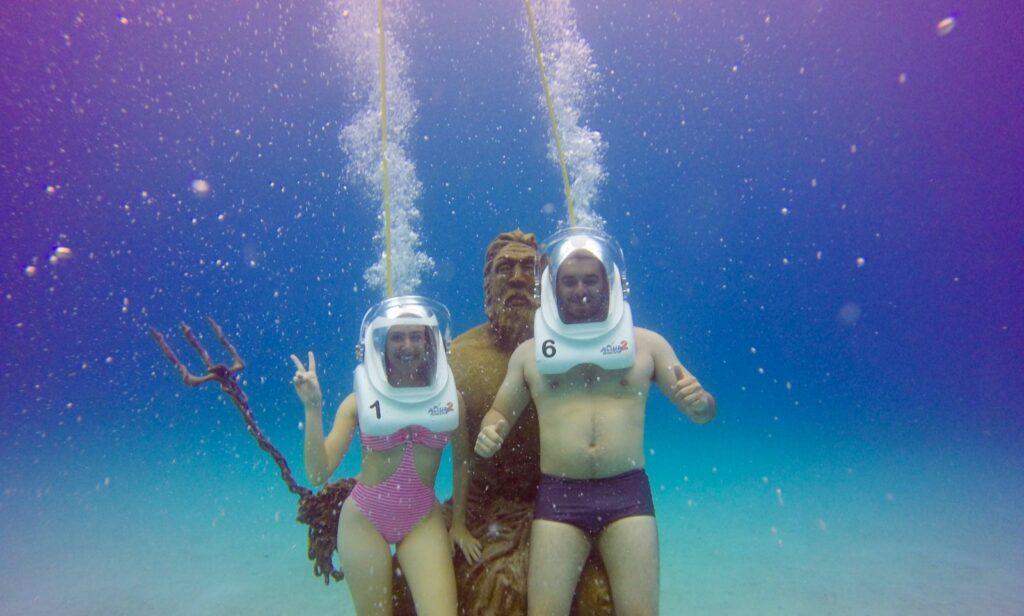 Casal mergulhando ao lado de Poseidon no Mar do caribe