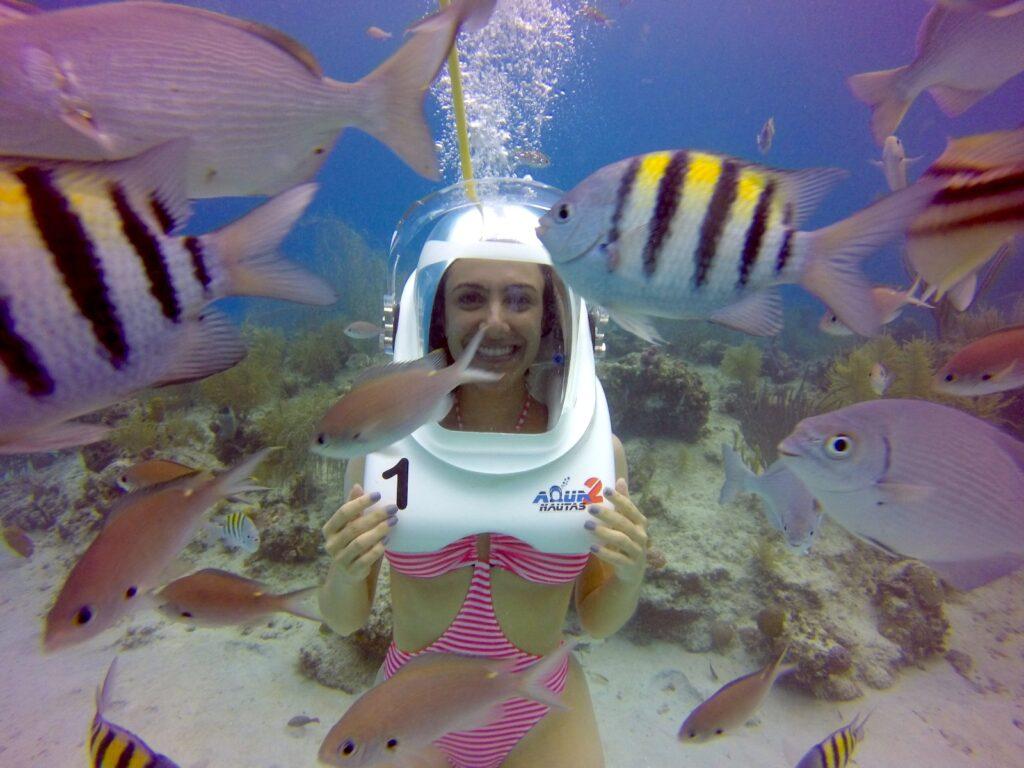 Mulher mergulhando no Mar do Caribe junto com peixes