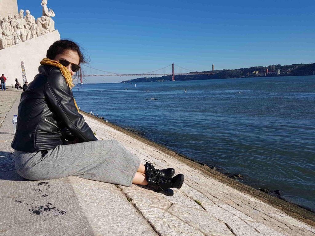 Mulher em Lisboa com mar e ponte ao fundo